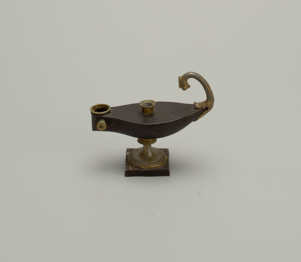 In shape of a boat, in antique manner, mounted on circular gilded foot with square black base; gilded handle, curved and terminating in animal's head.
