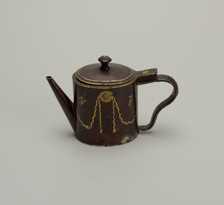 Oval, with straight spout and shaped handle. Brown field, with decoration in gilt of festooned foliage. Contains muslin bag for tea leaves.