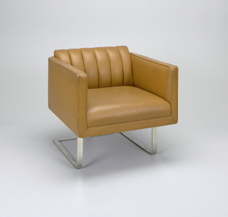Cube-form armchair on bent stainless steel base; tan leather upholstery with channel back; base and chair on spring construction.