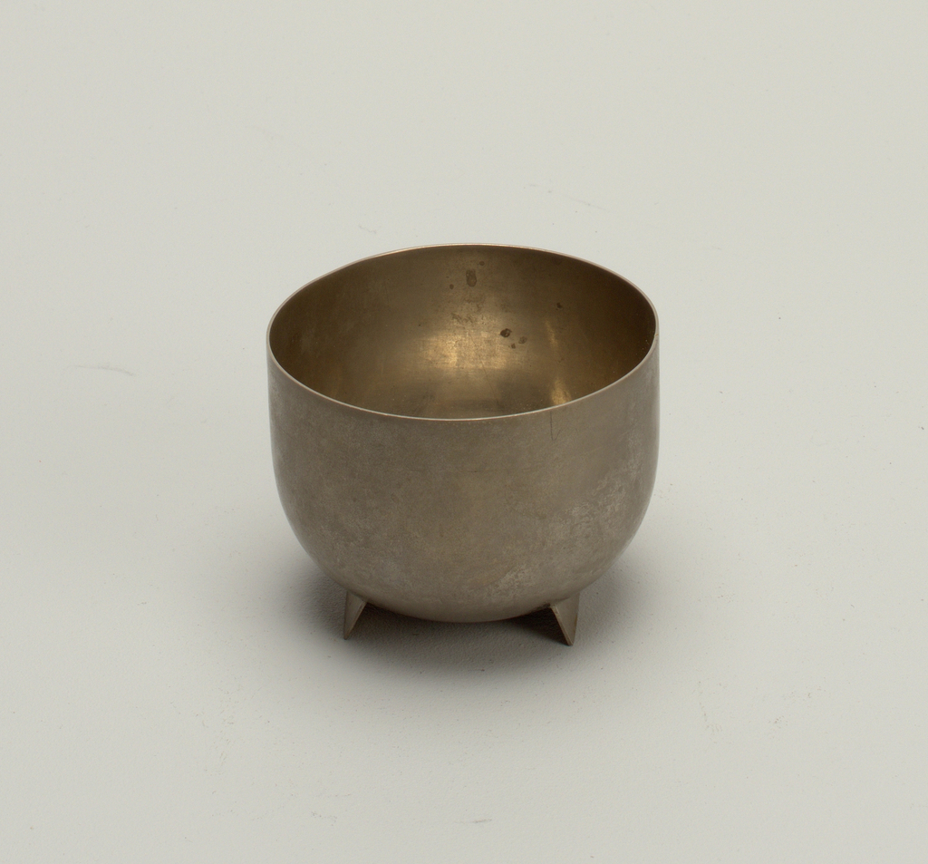Slightly oblong semi-spherical bowl with undecorated surface, atop flat feet of the same material. Surface is reflective but tarnished.
