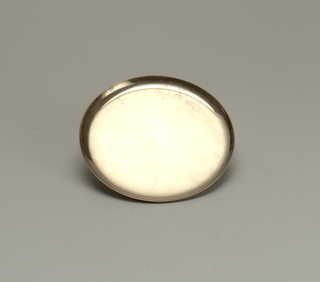 Circular plated metallic saucer with subtle curved lip. Surface is reflective but slightly tarnished and is free of any decoration or embellishment.