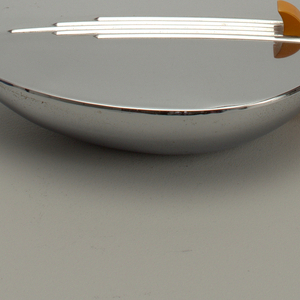 Leaf- or boat-shaped metal bowl and flat cover hinged at one end and attached to slightly curved Bakelite handle with molded striations; lid decorated with strip of striations; thumb piece and handle of deep yellow Bakelite.