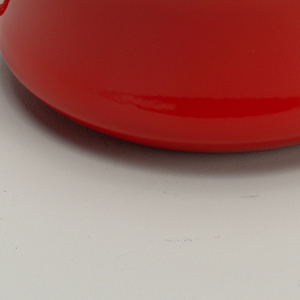 """Two-quart """"Kobenstyle"""" casserole. (a) Deep, round red enamel dish with handles on sides. Handle of cover formed in shape of an X. Inside of both A and B coated in white enamel."""