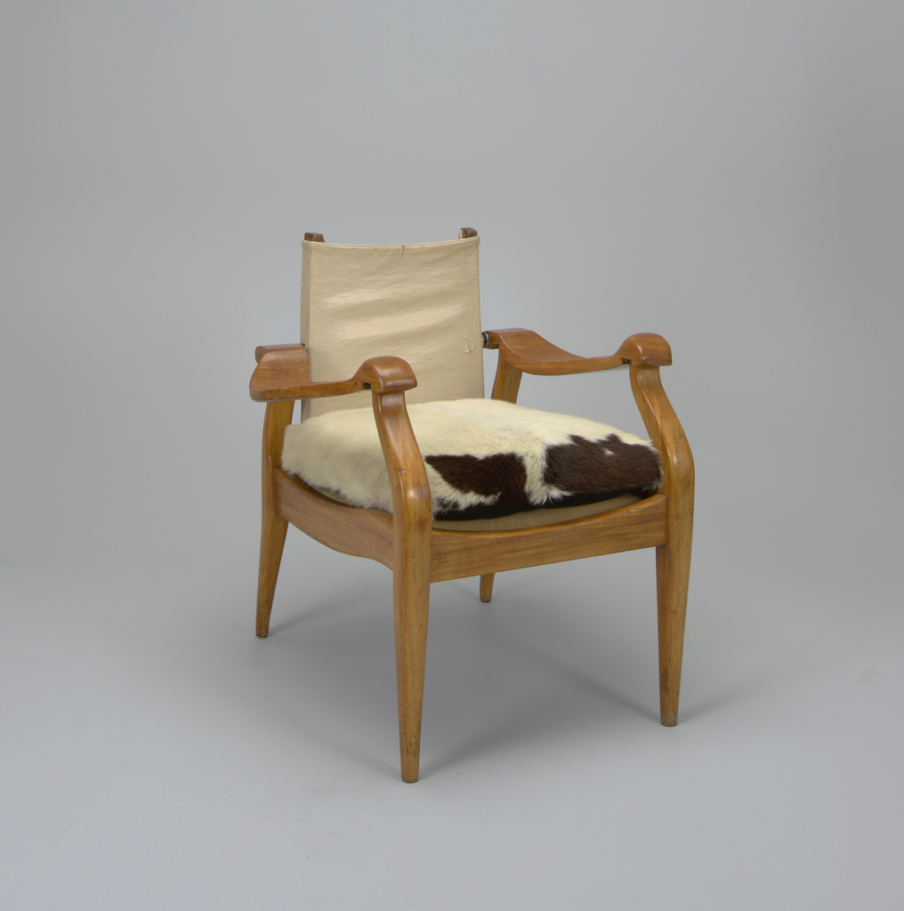 Wood frame with wide curved and shaped arms, deep rectangular seat and four tapered legs, the front legs angled back toward joint with arms; rectangular, pivoting seat back of tan leatherette stretched on metal and wood frame; rectangular seat cushion covered in pony skin, white with large irregular black spots on one end.