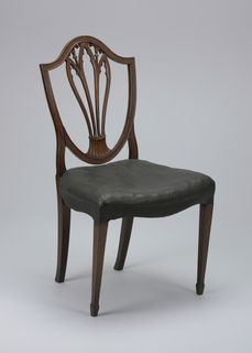 Shield back side chair with a splat composed of three open blade-forms; cusped on their interiors and separated under the top rail by two blossoms.  The forms merge into a fluted spreading panel at their base.  Its legs are straight, square, and tapered in the front on square feet.  The seat is shaped, hollowed, and upholstered in black-painted canvas (possibly the original upholstery).