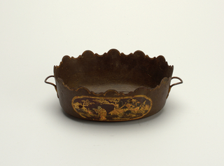 Oval, with shaped edge and simple wire handles. Neutral brown field, long elliptical medallions on front and back, enclosing Chinese landscape, in color and slightly in relief.