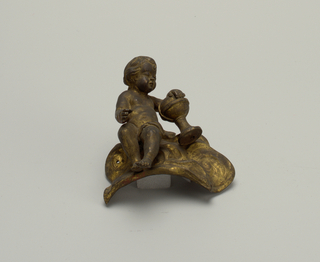 Seated child with one hand on a globe