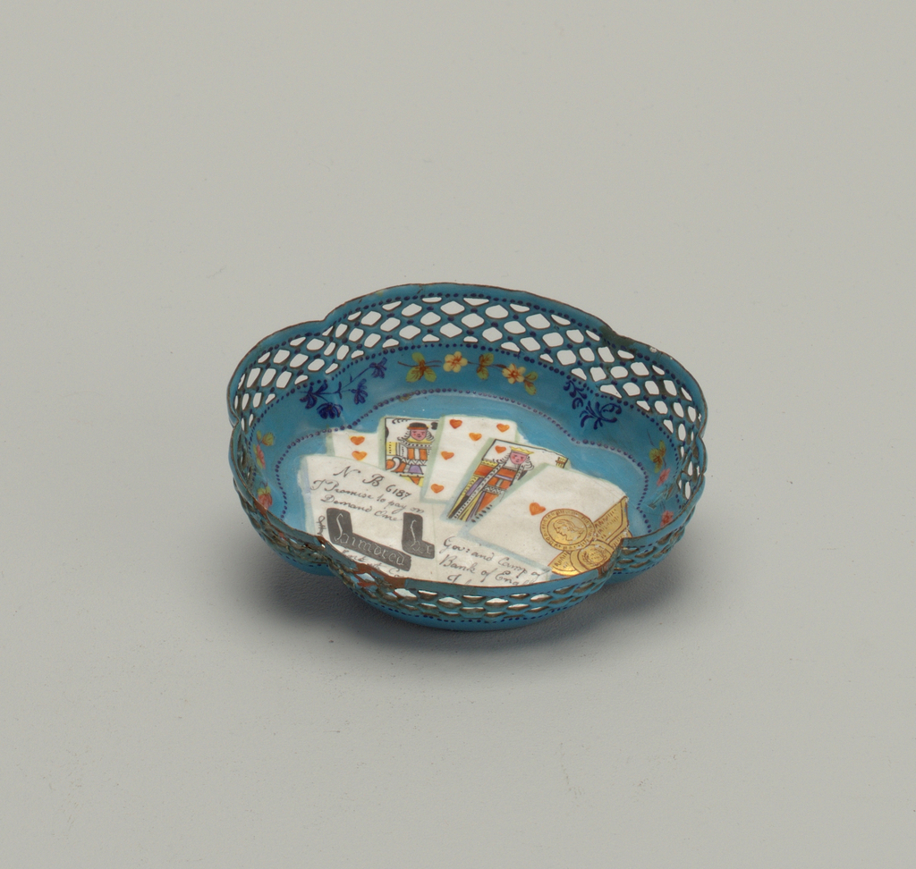 Lobed basket with pierced edges and blue enamel ground. Painted in polychrome and gold to evoke a gambling table, with bank-note, coins and playing cards.
