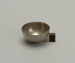 Semi-spherical bowl with metal cuff affixed to a rectangular wooden handle. Stabilizing feet at bottom. Slightly tarnished surface.