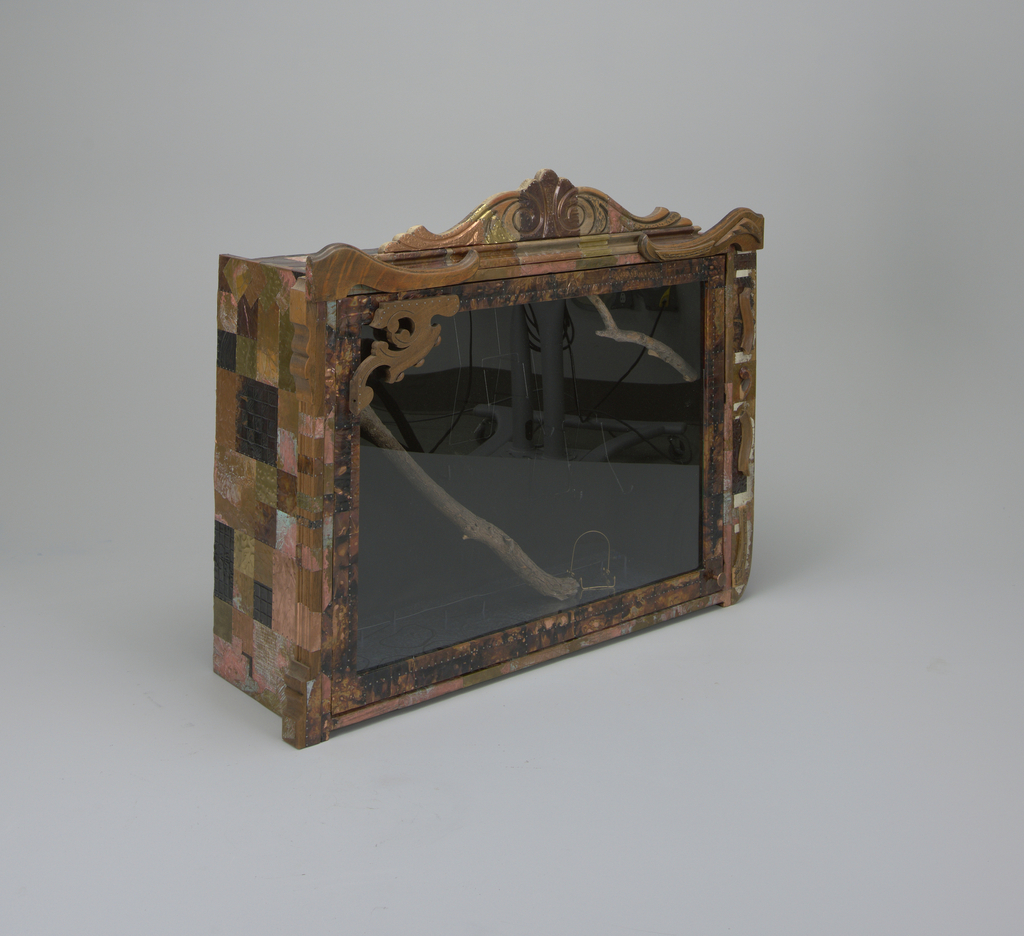 Wooden cabinet of rectangular form with large hinged plexiglass door, small circular knob at bottom right corner; front of cabinet decorated with applied pieces of found wood in various shapes and lengths forming decorative pediment and scrolls at top and sides; exterior surface decorated with applied small metal sheets, some embossed and patinated.  Cabinet holds 27-piece ceramic dinner service in forms of fish and water plants, glazed in various colors, arranged to depict aquarium scene, some fish 'swimming' amongst two wooden branches.