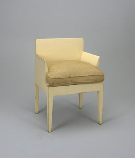 Squat, angular shaped chair.  Tapered arms and back; arm rests and back in a continuous plane with seat.  Off-white enamelled surfaces.  Cushion on seat only.