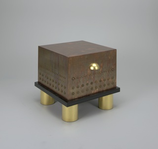 Box-shaped, finished with patinated copper leaf and studded with rows of brass nails, washers, and coins. Black enameled base resting on four cylindrial gilded feet. Semi-spherical gilt handle which pulls out deep drawer.