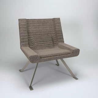 Stacked layers of cut wool felt laminated with water-based glue to form a solid form of set-back layers on four stainless steel legs set at angles to the upright rectangular outline of the chair.