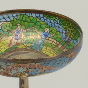 Circular, shallow open bowl with translucent plique à jour enamel, brightly multicolored, in which is depicted scene of couples dancing in landscape with windmill: on stem, with one raised banding just above point where stem spreads to form foot.  Base decorated with grapes, vine and leaves in enamel.