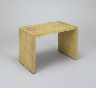Low table of natural colored parchment-covered wood with rectangular top and planar rectangular support at each end.