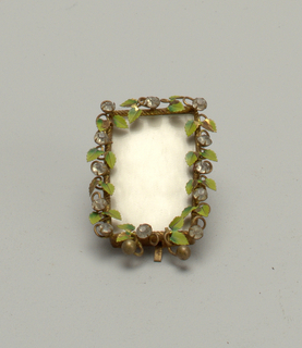 "Vertical rectangle of brass, having stemmed leaves painted green, and twelve glass ""diamonds"" set in prongs. Small brass spheres for feet. Tin sheet for back with brass rod for support."