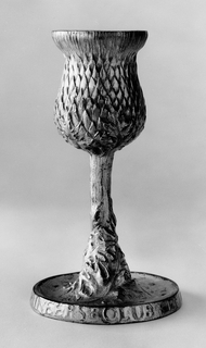 Cast gilt bronze goblet with artichoke pattern on exterior; thick foot with letters; stem is plant-like.