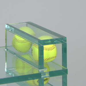 Rectilinear form of thick, polished Plexiglass with green edges; moveable seat flanked on left and right by two sets of softballs, above and below; seat lowers with sitters' weight, making it possible for sitter to rock on lower set of softballs.