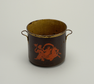 Cylindrical, with slightly rounded bottom and simple handles. Black field, with gilt decoration on handles and around edge, and on each side. At center, a red female figure on a seahorse.