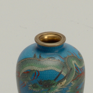 Slender gallipot shape, with green and white dragon pursuing the flaming pearl, in aventurine enamel, on a blackground of blue, scrolled with silver wire. Neck and foot mounted in brass. Yellow counterenamel.