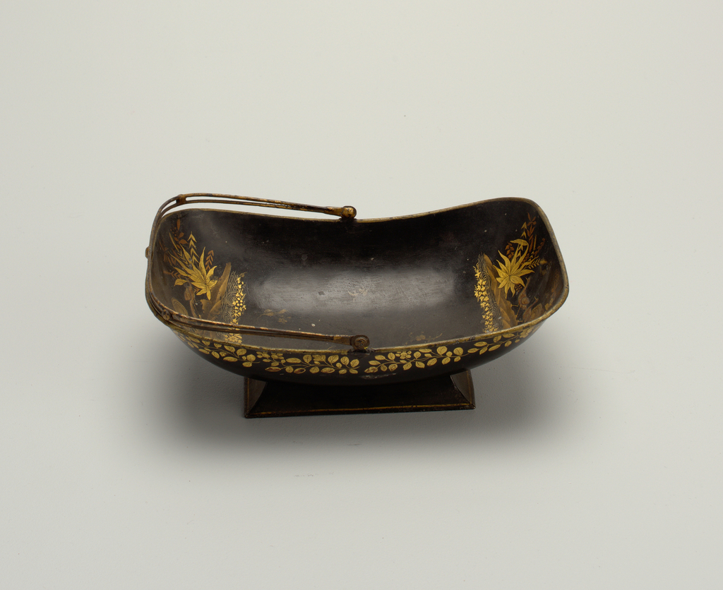 Rectangular, with rounded bottom, on rectangular foot. Openwork wire handle. Black field decorated in gilt, about outside, band of roses and foliage; inside, at either end, peacocks and foliage.