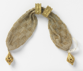 Crocheted white silk ornamented with gold beads in all-over checkerboard pattern.  Two gold rings with foliate decoration control side opening; fancy gold drops at each end.