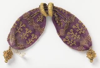 Violet-red crocheted silk ornamented with gold beads in pattern of sprigs and diamond-shaped bars. Side opening controlled with two gold rings with rose pattern in relief. Gold filigree work at each end.