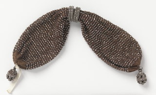 Crocheted brown silk, evenly ornamented with cut steel beads. Two rings of cut steel control a side opening. Fancy drops of cut steel at each end.