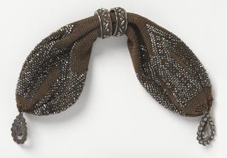 Crocheted dark brown silk ornamented with cut steel beads in geometric pattern.  Two cut steel rings control side opening; steel pendant at each end.