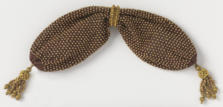 Netted brown silk, evenly ornamented with gold beads.  Side opening controlled by two gold rings.  Small gold ball and bead tassel drops at each end.