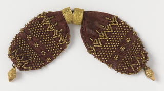 Crocheted maroon silk decorated with bands of gold beads in stylized patterns.  Two gold rings, with floral patterns in relief, control the side opening. Gold pendant at each end.