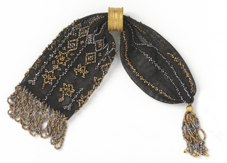 Crocheted black silk ornamented on one end with single lengthwise bars of alternating rows of gold and cut steel beads; the other end is decorated with gold and steel beads in a six-pointed star and diamond pattern. One gold ring controls side closing. One end is fringed, the other tasseled, both with cut steel and gold beads.