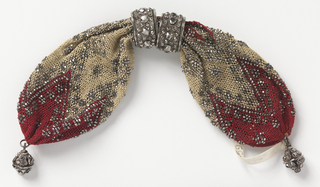Silk net bag with red triangular pattern at each end, white silk in the middle. Ornamented with cut steel beads outlining the triangles and forming diamond-like designs on the mid portion. Two heavily cut rings control side opening; cut steel drops at either end.