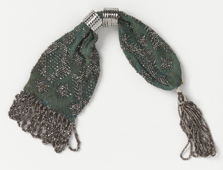 Crocheted dark green silk embroidered with cut steel beads in diamond patterns.  Two steel rings control side closing; at one end, a bead tassel, at the other, fringe of twisted bands. Both are made of cut steel.