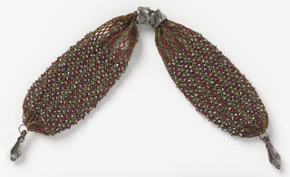 Silk, crocheted in lengthwise narrow bars of red and green, ornamented evenly with cut steel beads. Two steel rings control side closing; steel drops at either end.