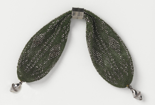 Crocheted dark green silk ornamented with cut steel bands in bar and diamond pattern. An octagonal steel ring controls side closing; faceted steel drops at each end.