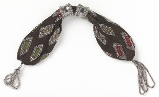 Netted silk of very dark brown with rectangular inserts of green, tan and red in rectangular patterns, which are outlined with beads of cut steel.  Two ornate rings of cut steel control side opening; steel tassels (one twice as long as the other) at each end.