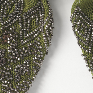 Crocheted yellowish-green silk heavily ornamented with cut steel beads in various diamond patterns. Two faceted steel rings control side closure; steel drops at each end.