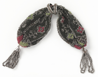 Crocheted black silk embroidered with small red and green squares, outlined in steel beads.  More steel beads form bars and crosses.  Side closing controlled by two steel rings; steel bead tassels at each end of purse.