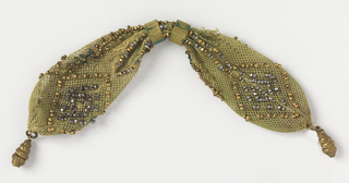 Crocheted pale green silk decorated with gold and cut steel beads in diamond pattern. Two gold rings control side opening; twisted shell-shaped drops at each end.