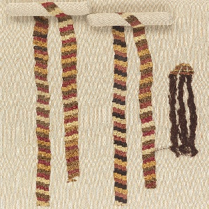 Narrow slit tapestry strip with adjacent diagonal stepped repeats in white, rose reds, browns, golden yellow. One end finished with attached long tassel of brown wool yarns joined at top by a small piece of plaited casing, and the other with a wound casing in yellow, brown, red wool.