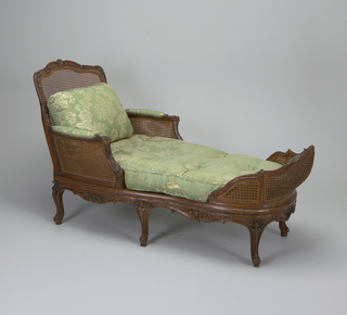 Carved and caned; the frame elaborately carved with clusters of blossoms, frilled scrolls, and trailing leaves, the arm pads, black and seat  cushions in green brocade.