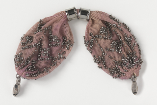 Crocheted mauve silk ornamented with cut steel beads in geometric pattern. Two round steel rings control the side opening. Small steel drops at each end.