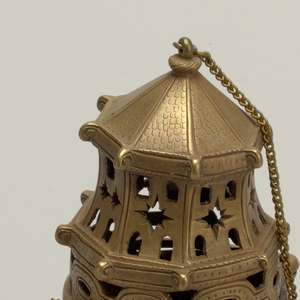 A panelled octagonal foot resolves into a twisted knop to a round gadrooned bowl, the upper rim of which bears four pierced lugs to receive chains.  The lugs are matched on the base of the pierced top which is in the general form of an octagonal tower with voluted beam ends and an imbricated faceted roof.