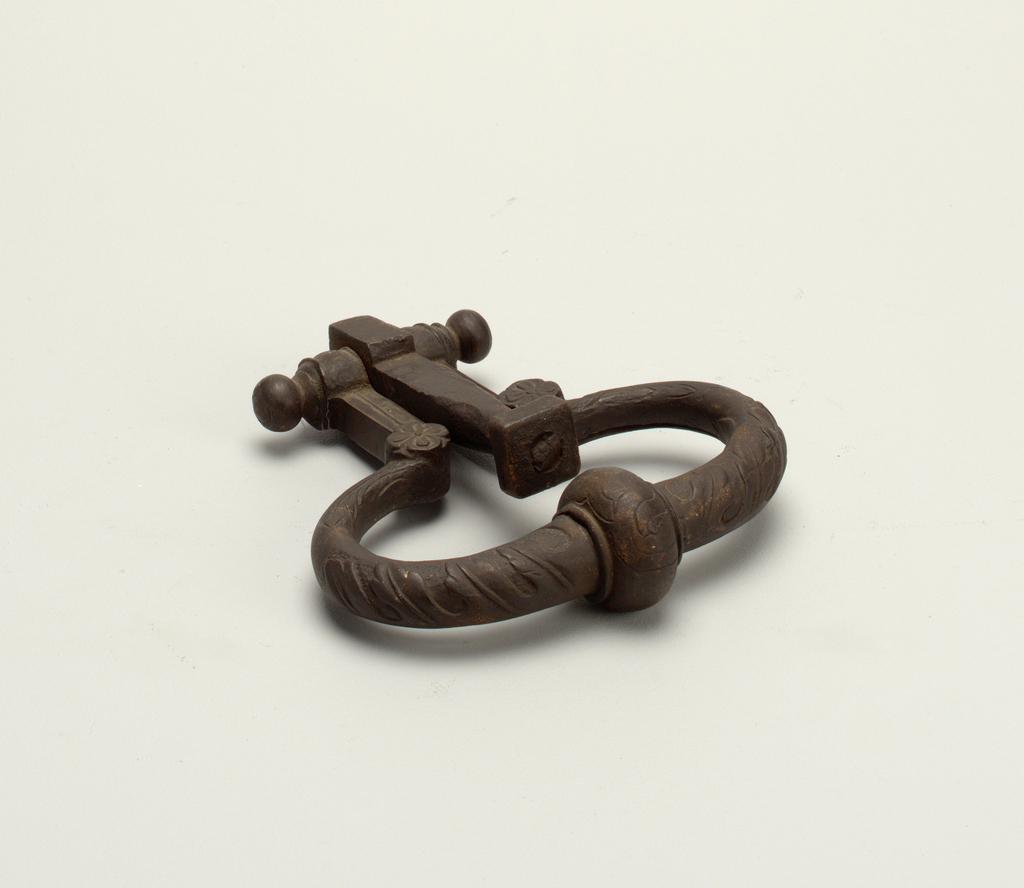 Door knocker. Large bead at lower center. Handle decorated with leaves in relief. Two rosettes at top of handle.