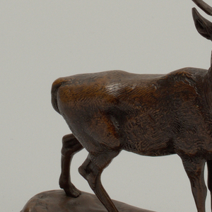 a) Statuette of a stag, standing with head raised, two front feet close together, right rear foot advanced.  Statuette attached with nuts and screws to hollow bronze base,  rectangular with rounded corners. b) Wooden base, rectangular, with chamfered corners.