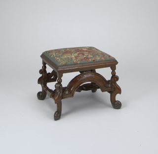 In William and Mary Style. Scroll legs and feet, carved back and front stretchers. Turned stretchers at sides are united by shaped and pierced stretcher of unusual design, probably a modern replacement. Slip seat covered with tapestry with flowers in natural colors.