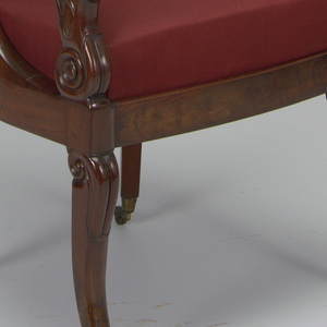 Straight-sided front legs, set square, curving outward toward voluted foot; lotus leaf carved on knee, with volute in side of knee.  Back legs square in section, curving outward from center.  Plain veneered seat rail semicircular about back, straight on sides, slightly bowed on front.  Back, with ogive cresting, descends in forward curve to seat rail.  Arms, round in section, terminate in volute supported by conventionalized lotus flower springing from volute and lotus leaf resting on front leg.  Chair upholstered on both sides of back and on boxed slip seat, with red silk damask edged with brocaded trimming in red and yellow.