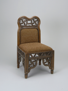 Side chair with upholstered seat and back in brown leaf pattern. Frame surrounding back: two lobes bordering circles of lattice work decorated with trefoils; same lobes present at legs, above which is a lattice work stretcher on all four sides of chair.