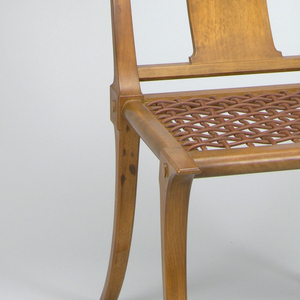 The chair has a concave backrail and leather webbed seat, raised on splayed, tapering legs.  The backrail is supported by a back splat of similar thickness, placed perpendicular to the crest rail.